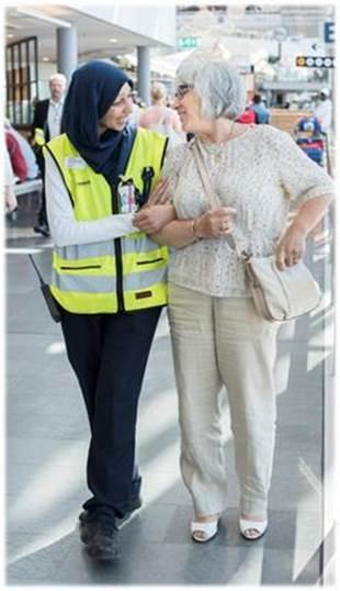 Bild på en av Swedavias ledsagare som assisterar en resenär.