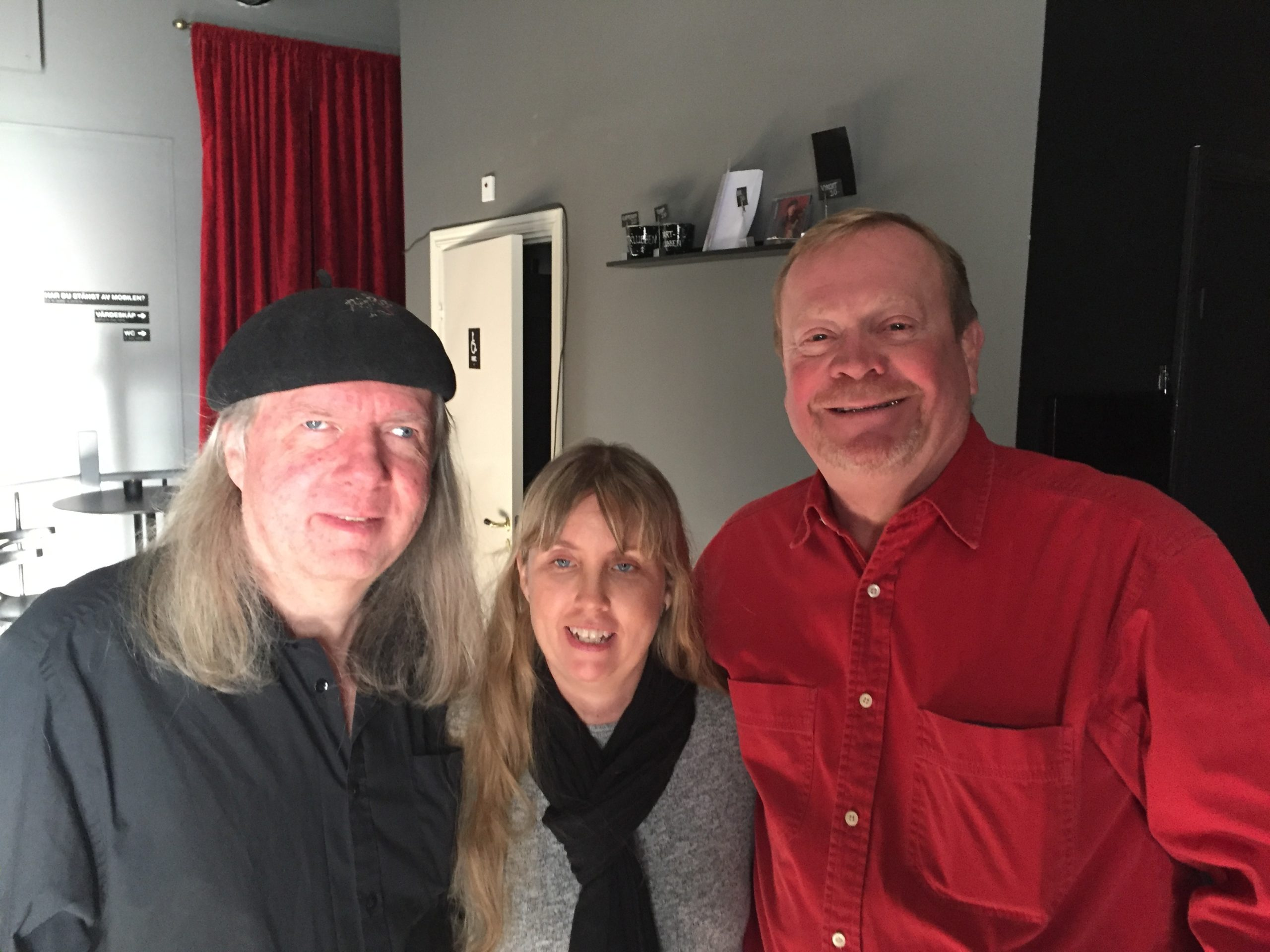 Ulf, Anna och Jonas i studion. Gråa väggar och ett rött drapperi i bakgrunden. Ulf har svart basker, långt grått hår och en svart skjorta. Anna har långt blont hår, en svart halsduk och en grå tröja. Jonas har kort ljust hår och en röd långärmad skjorta.