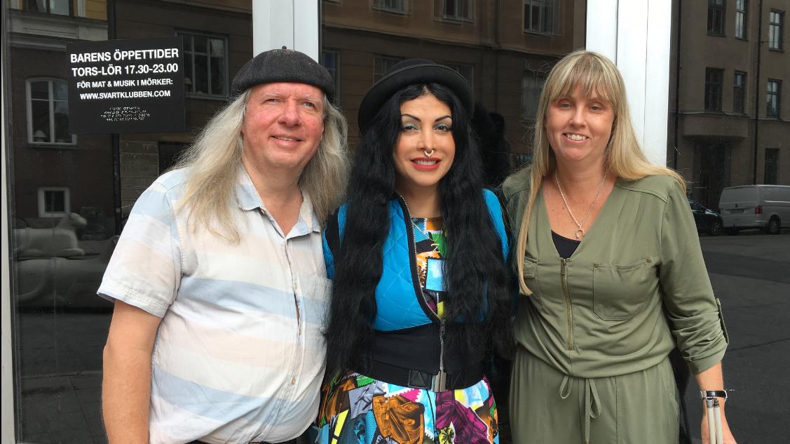 Ulf, Zinat och Anna står utomhus mot svarta glasrutor. Ulf har långt grått hår, svart basker och ljus kortärmad skjorta. Zinat har en svart hatt, långt svart hår, en ring i näsan och är klädd i en blå tjock klänning med färgglada mönster. Anna har långt blont hår och en grön byxdress.