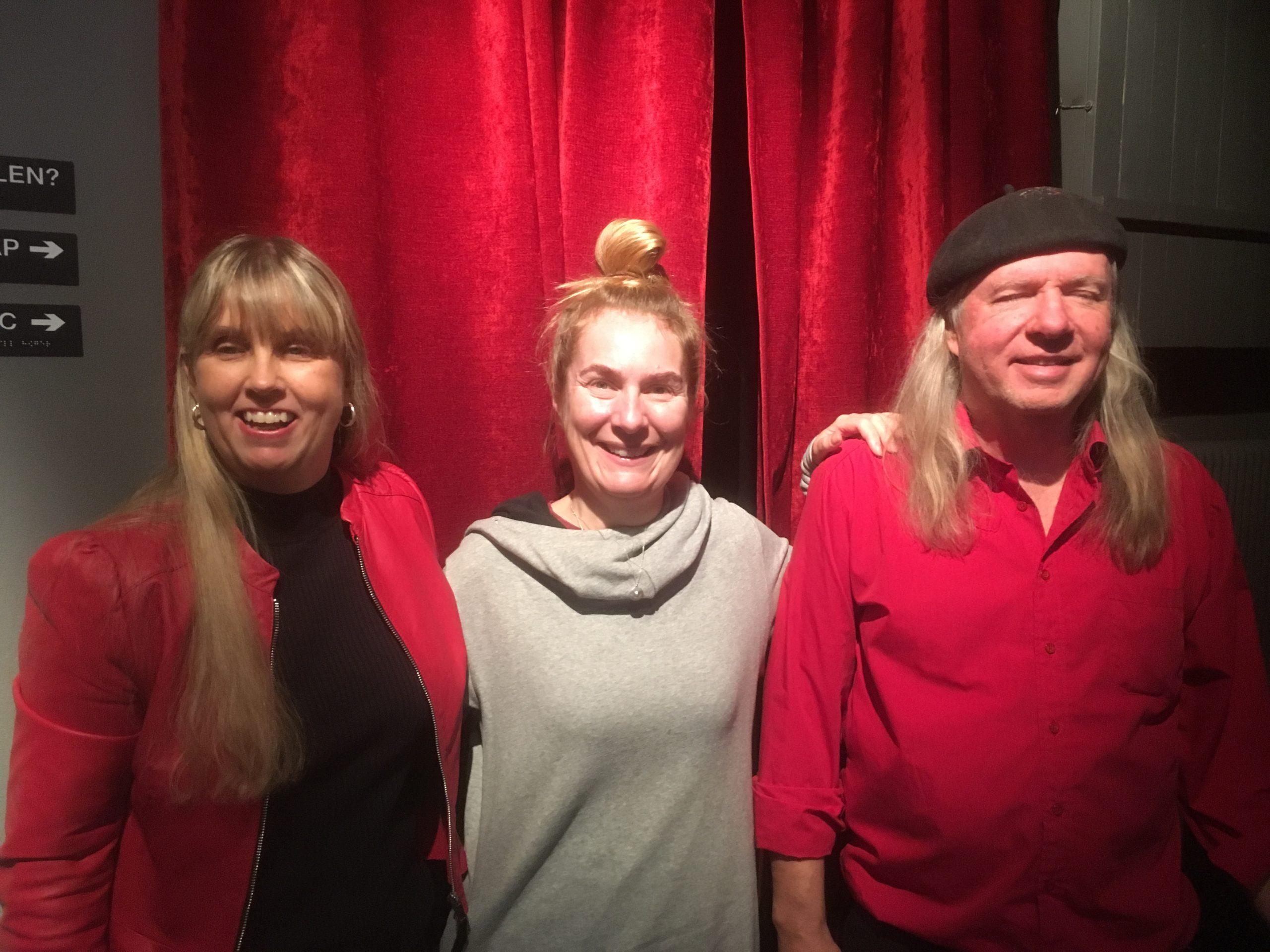 Anna, Annika och Ulf, gruppfoto med röda gardiner som bakgrund. Anna har långt blont hår och har på sig en röd jacka samt en svart polotröja under. Annika har uppsatt ljust långt hår i en toffs och klädd i en ljusgrå tröja. Ulf har långt grått hår, svart basker och en röd lågärmat skjorta.