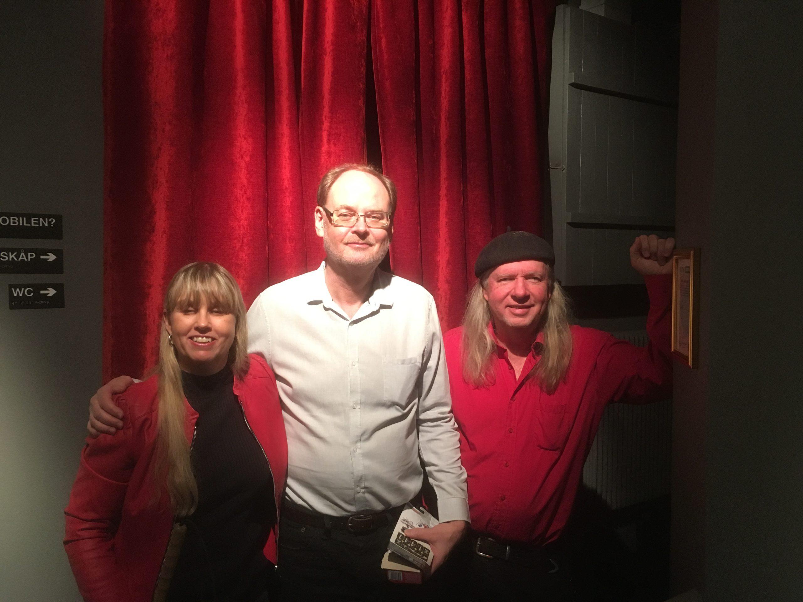 Anna, Clas och Ulf, gruppfoto med röda gardiner som bakgrund. Anna har långt blont hår och har på sig en röd jacka samt svart polotröja. Clas har kort ljusbrunt hår, glasögon och är klädd i en vit skjorta och svarta byxor. Ulf har långt grått hår, svart basker, röd långärmad skjorta och mörka byxor.