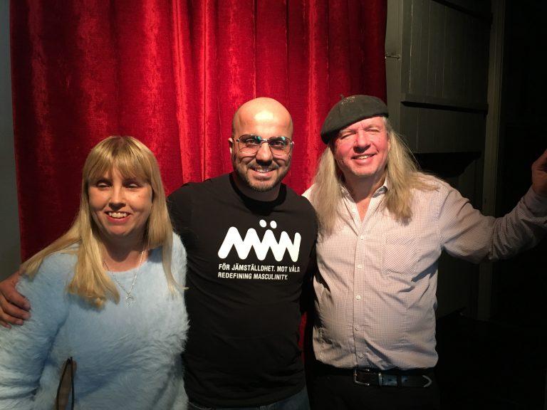 Anna, Alán och Ulf, gruppfoto med röda gardiner som bakgrund. Anna har långt blont hår och en ljusblå tjock tröja. Alán har rakat huvud, glasögon och en svart tröja med texten: Män, För jämställdhet, mot våld. Redefining masculinity