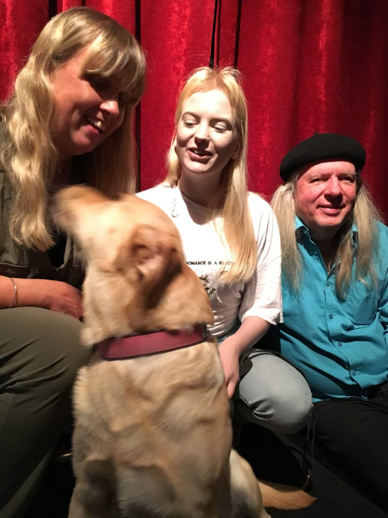 Anna, Smilla och Ulf med hunden Chanti, en ljus labrador. Anna har långt blont hår och en grön byxdress. Smilla har långt blont hår, vit t-shirt och ljusblå jeans. Ulf har en svart basker, långt grått hår, turkos skjorta och mörka byxor.