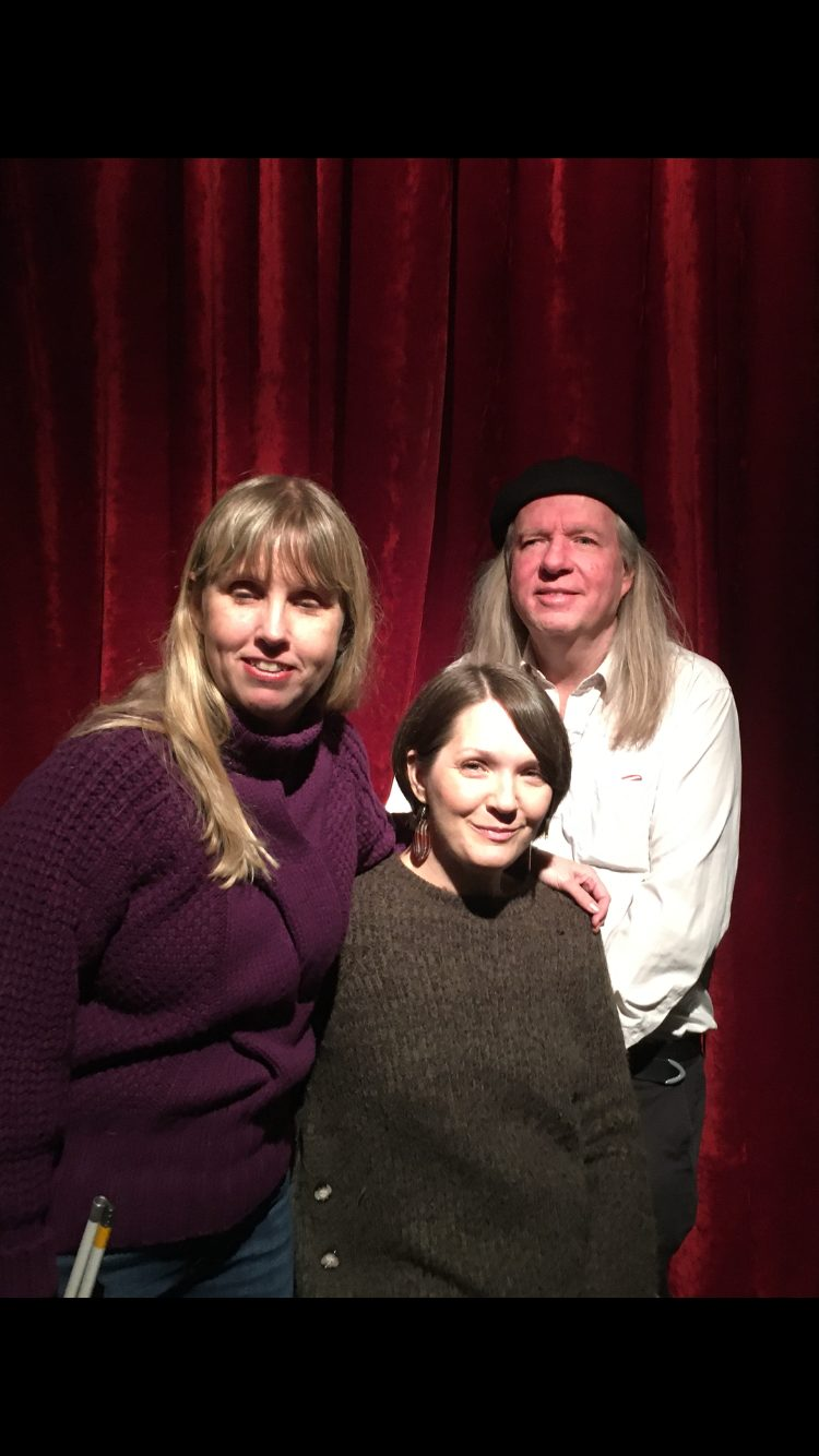 Anna, Yasmin och Ulf gruppfoto med röda gardiner som bakgrund. Anna har långt blont hår och har på sig en lila långärmad tröja. Yasmin sitter ned och har på sig en långärmad gråbrun tröja samt halvlångt brunt hår. Ulf har långt grått och, vit skjorta och mörka byxor.