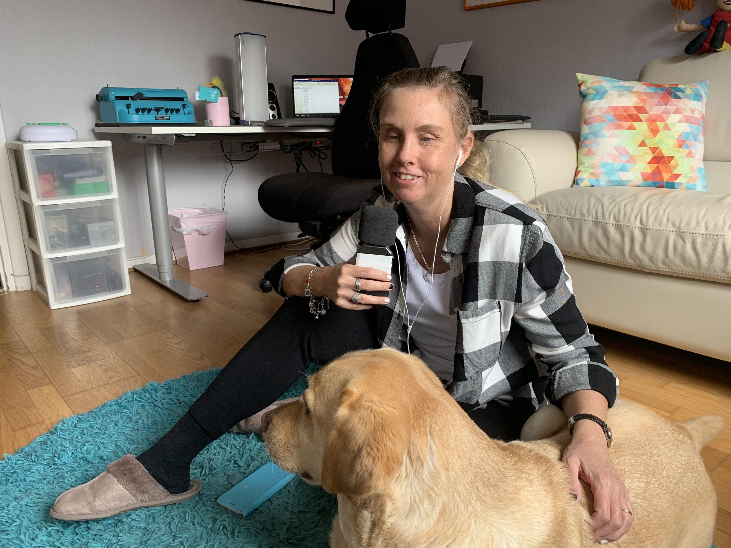 Anna sitter på golvet med sin ledarhund Chanti, en ljus labrador