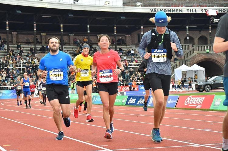 Fatmir i blå t-shirt och svarta shorts springer på löparbana på en arena