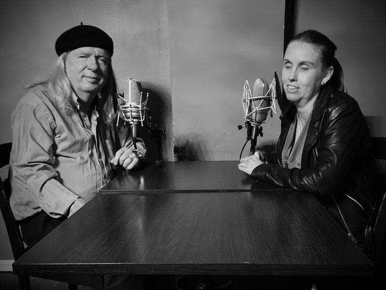 Ulf och Anna sitter i podcaststudion med var sin mikrofon mitt emot varandra vid ett mörkt träbord. Båda tittar mot kameran och ler. Ulf har långt ljust hår, mörk basker, ljus skjorta och mörka byxor. Anna har långt blont hår, en svart skinnjacka, ovanpå en v-ringad överdel.